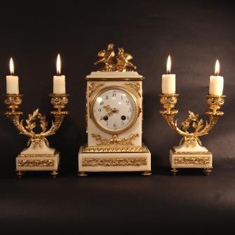 French striking mantel clock garniture of white marble and ormolu. Circa 1900.