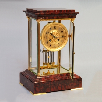 French four glass striking mantel clock in an ormolu and marble case. Circa 1900.