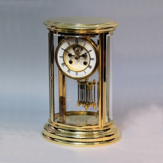 French, four glass, gilded oval mantel clock with visible escapement. Circa 1880.