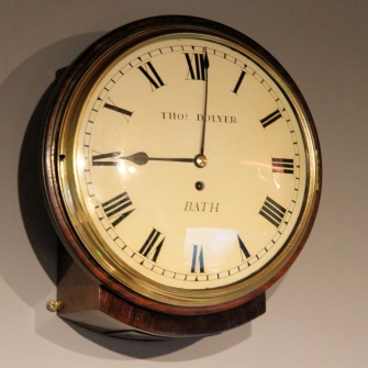 Early English dial clock with a rare bowed wooden dial and sheraton style bezel. Circa 1825.